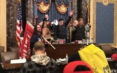 QAnon shaman Jake Chansley (L) leads fellow rioters in prayer from the dais of the US Senate on January 6, 2021 (Screencapture/YouTube)