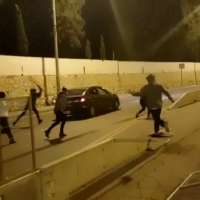 Demonstrators attack an Arab car in Jerusalem during a protest in the early hours of January 1, 2021. (Screenshot: Twitter)