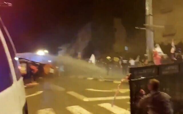 Police fire a water cannon against protestors they say tried to break through checkpoint and injured an officer, January 30, 2021 (Screen grab/Twitter)