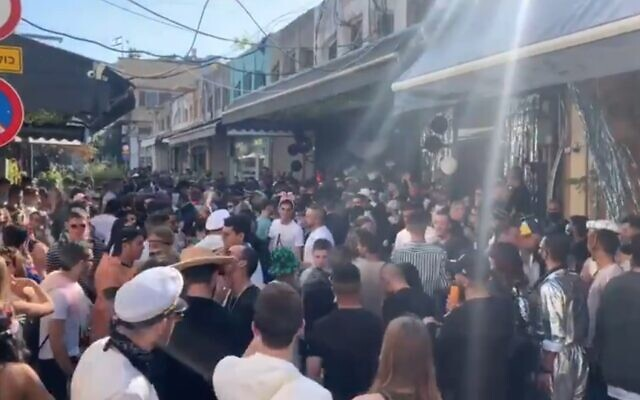 People celebrate the holiday of Purim in violation of coronavirus restrictions, at Jaffa's Flea Market in Tel Aviv-Jaffa, February 27, 2021 (video screenshot)