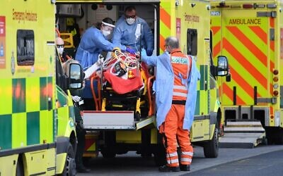 London Ambulance staff stretcher a patient from the ambulance into The Royal London Hospital in east London, on January 2, 2021. (DANIEL LEAL-OLIVAS / AFP)
