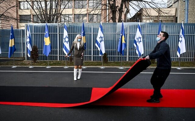 A Kosovo worker drags the red carpet next to Kosovo's and Israel's flags displayed during a ceremony at the headquarters of the Foreign Ministry in Pristina on February 1, 2021 (Armend NIMANI / AFP)