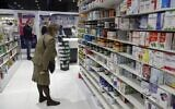 Customers browse the aisles for medicine at a pharmacy in the Lebanese capital Beirut, on February 2, 2021. (JOSEPH EID / AFP)
