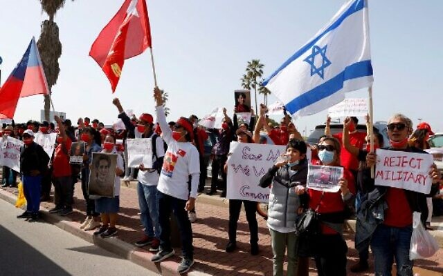 A group of Myanmar activists residing in Israel wave (L to R) the historical flag of Burma (until 1974), the flag of ousted leader Aung San Suu Kyi's National League for Democracy party, and the flag of Israel, during a protest outside the country's embassy in the Mediterranean coastal city of Tel Aviv on February 3, 2021. (JACK GUEZ / AFP)