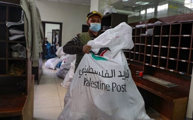 An employee of Palestine Post carries a courier bag at a post office in the West Bank town of Nablus, on February 7, 2021. (JAAFAR ASHTIYEH / AFP)