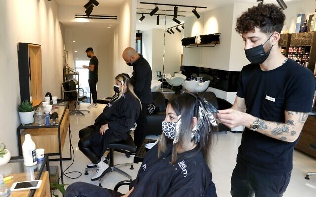 Women get their hair styled at a salon in Tel Aviv on February 7, 2021, following the lifting of a nationwide lockdown due to the COVID-19 pandemic. (JACK GUEZ / AFP)