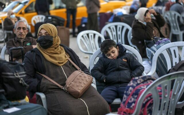 A mask-clad Palestinian woman and a boy wait with luggage at the Rafah border crossing's departure area to travel from the Gaza Strip into Egypt, on February 9, 2021. (Said Khatib/AFP)