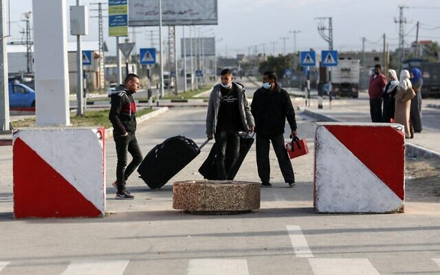 Palestinians walk with luggage at the Rafah border crossing's departure area to travel from the Gaza Strip into Egypt, on February 9, 2021 (SAID KHATIB / AFP)