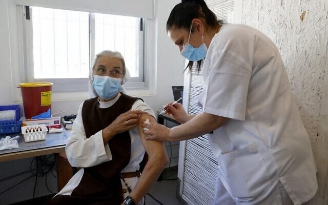 A French nun living in Israel receives a dose of COVID-19 coronavirus vaccine at the Tel Aviv Sourasky Medical Centre for foreign nationals in Tel Aviv on February 9, 2021 during a campaign to vaccinate foreign workers and refugees against coronavirus. (JACK GUEZ / AFP)