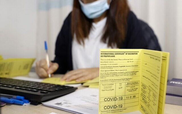 In this file photo taken on December 19, 2020 an Israeli medical worker fills an international certificate of vaccination for coronavirus at the Sheba Medical Center, the country's largest hospital, in Ramat Gan near the coastal city of Tel Aviv. (JACK GUEZ / AFP)