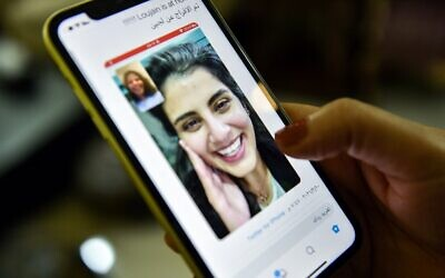 This picture taken February 10, 2021 in Saudi Arabia's capital Riyadh shows a woman viewing a tweet posted by the sister of Saudi activist Loujain al-Hathloul, Lina, showing a screenshot of them having a video call following Hathloul's release after nearly three years in detention (Fayez Nureldine / AFP)