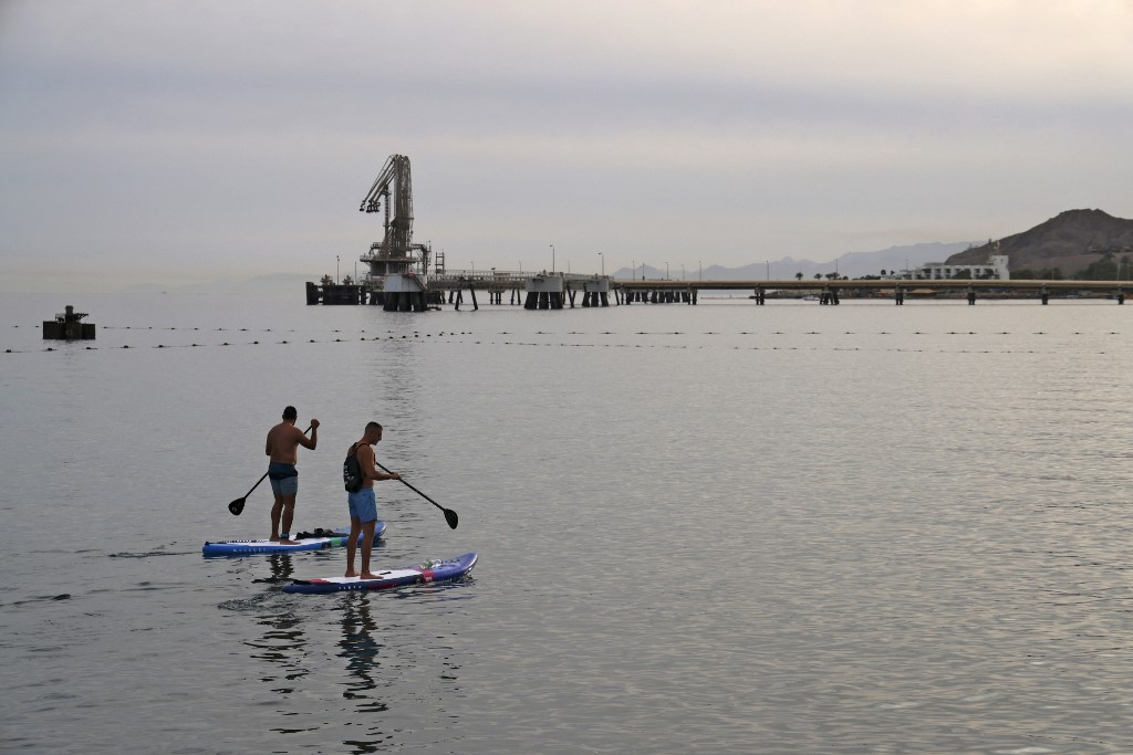 Men row on standup paddle boards in the Red Sea waters near the Eilat-Ashkelon Pipeline Company's (EAPC) oil terminal by Israel's southern port city of Eilat on February 9, 2021. (MENAHEM KAHANA / AFP)