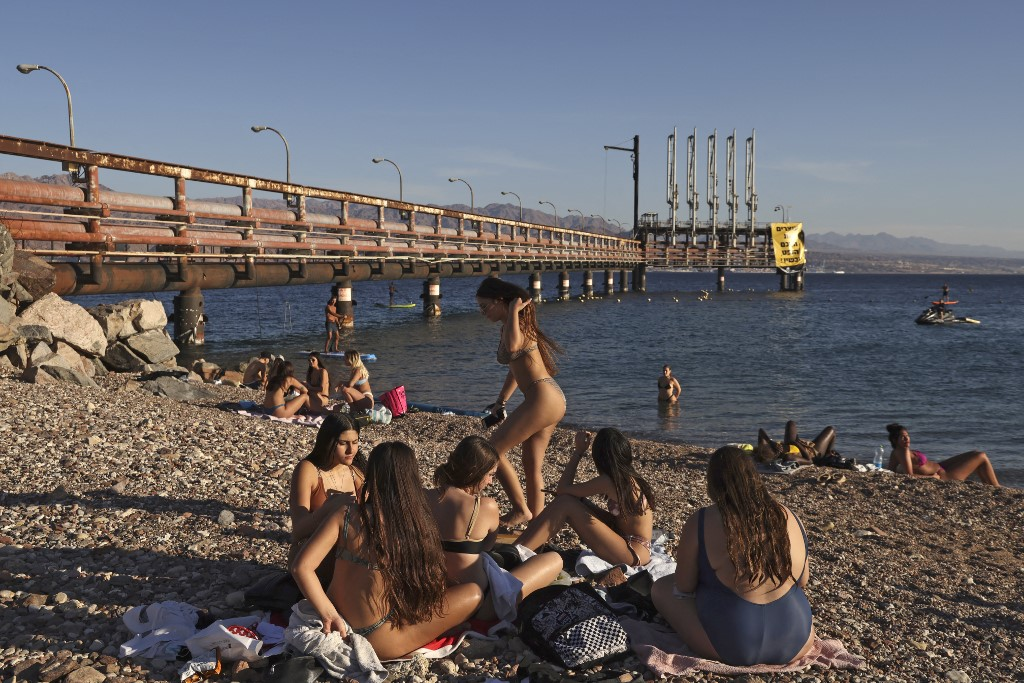Youths sit together at a Red Sea beach by an abandoned oil jetty in Israel's southern port city of Eilat on February 10, 2021. (MENAHEM KAHANA / AFP)