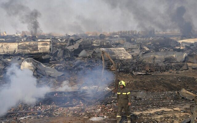 A firefighter walks amidst wreckage of gas tankers after a fire accident at Islam Qala on the outskirts of Herat, in the border between Afghanistan and Iran on February 14, 2021. (HOSHANG HASHIMI / AFP)