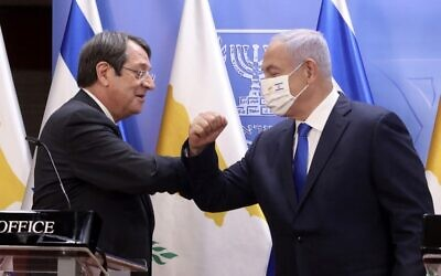 (L to R) Cyprus' President Nicos Anastasiades elbow-bumps Prime Minister Benjamin Netanyahu (mask-clad), during a joint press statement after their meeting at the Prime Minister's Office in Jerusalem on February 14, 2021. (Marc Israel SELLEM / POOL / AFP)