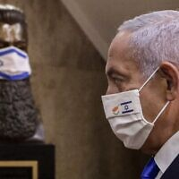 Prime Minister Benjamin Netanyahu at the Prime Minister's Office in Jerusalem on February 14, 2021, in front of a mask-clad bust of Theodor Herzl, the founder of modern Zionism. (Marc Israel Sellem/Pool/AFP)