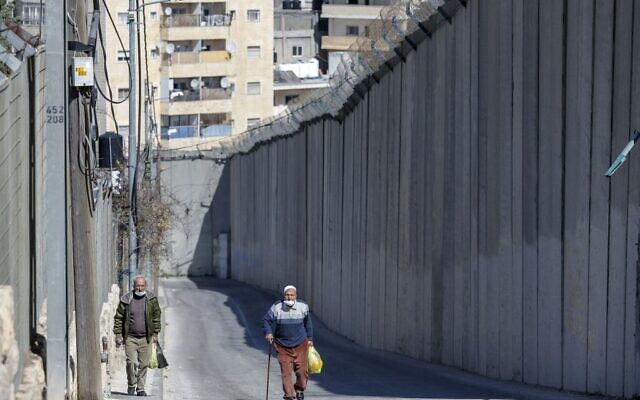 Palestinian men walk by Israel's security barrier separating Abu Dis (background) and East Jerusalem (foreground), on February 16, 2021. (AHMAD GHARABLI / AFP)
