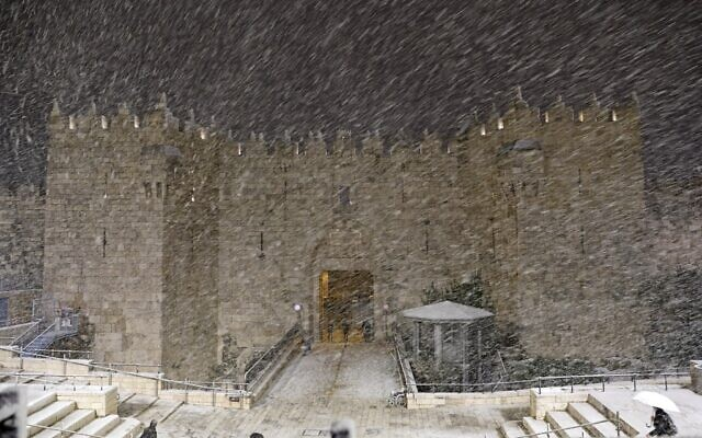 Snow falls at the Damascus Gate in Jerusalem's Old City, February 17, 2021. (Ahmad GHARABLI / AFP)