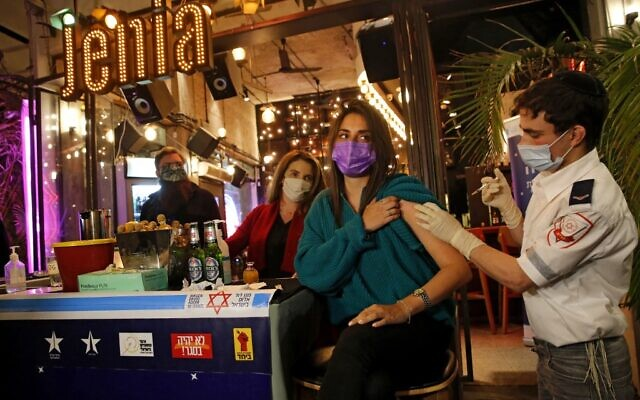 A health worker administers the COVID-19 vaccine to an Israeli at a bar in Tel Aviv on February 18, 2021. (GIL COHEN-MAGEN / AFP)