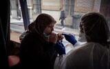 A patient (L) is watched by a medical assistant as she spits into a test tube for a COVID-19 saliva test on a roving bus in Saint-Etienne, France, on February 22, 2021. (Jean-Philippe Ksiazek/AFP)
