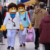 People dressed as Lego medical workers walk past shops in Jerusalem on February 24, 2021, a day before the Jewish holiday of Purim. (Emmanuel Dunand/AFP)