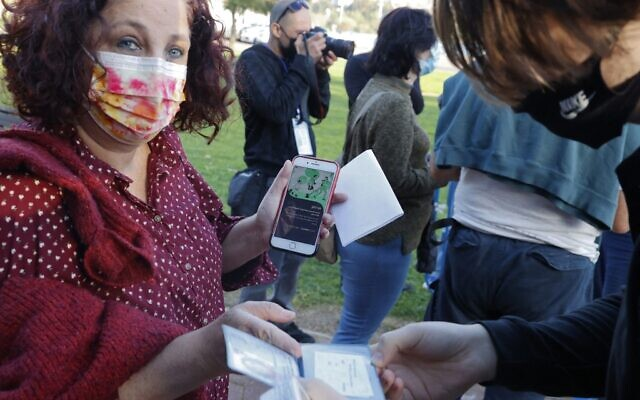 A woman shows her 'Green Pass' before entering a concert for vaccinated seniors, organized by the municipality of Tel Aviv, on February 24, 2021. (JACK GUEZ / AFP)