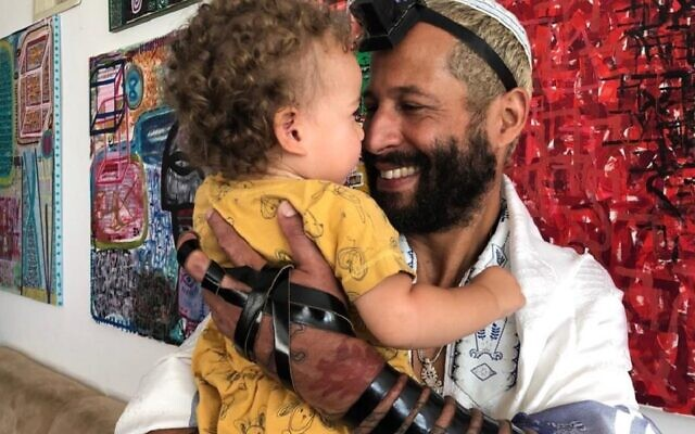 Alander Especie, shown with his daughter Liz, puts on tefillin every day. (Courtesy of Especie/ via JTA)