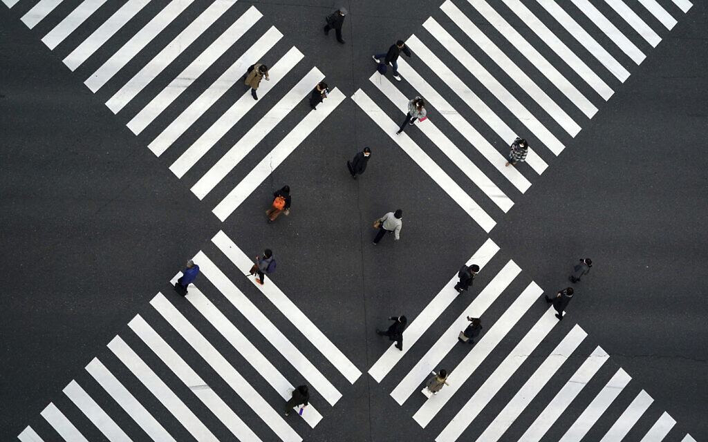 People wearing protective masks to help curb the spread of the coronavirus walk along pedestrian crossings in the Ginza shipping area of Tokyo, January 8, 2021. (AP Photo/Eugene Hoshiko)