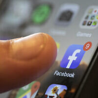 An iPhone displays the Facebook app, August 11, 2019.  (AP Photo/Jenny Kane, File)