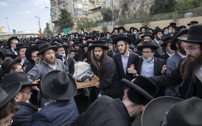 Ultra-Orthodox Jews carry the body of Rabbi Meshulam Soloveitchik during his funeral in Jerusalem, Sunday, Jan. 31, 2021. The mass ceremony took place despite the country's health regulations banning large public gatherings, during a nationwide lockdown to curb the spread of the virus. (AP Photo/Ariel Schalit)