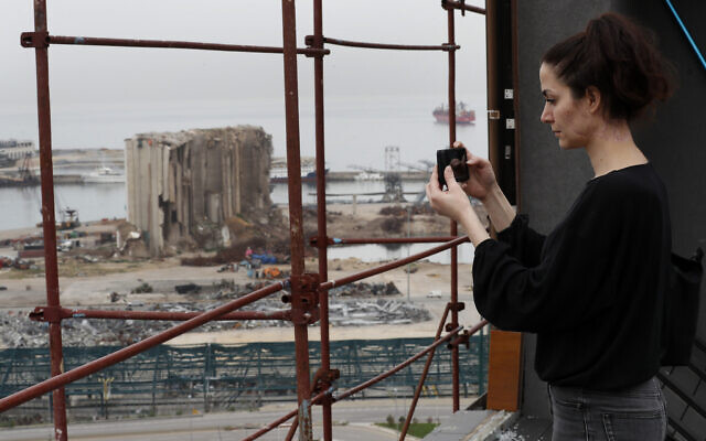 Joana Dagher, 33, who lost her memory for two full months from the trauma she suffered in the massive August explosion at the Beirut port, including a cerebral contusion and brain lesions, takes pictures of the explosion scene from her damaged apartment rooftop, in Beirut, Lebanon, January 27, 2021. (Hussein Malla/AP)