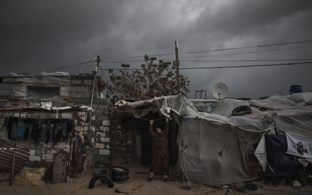 A Palestinian woman checks the nylon cover on the roof of her house on a rainy day in a poor neighborhood of Khan Younis, in the southern Gaza StripJan. 20, 2021. (AP Photo/Khalil Hamra, File)