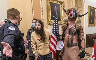 In this Wednesday, Jan. 6, 2021 file photo, supporters of President Donald Trump, including Jacob Chansley, right with fur hat, are confronted by US Capitol Police officers outside the Senate Chamber inside the Capitol in Washington.(AP Photo/Manuel Balce Ceneta)