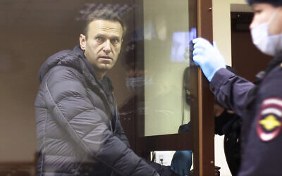 In this image made from video provided by the Babuskinsky District Court, Russian opposition leader Alexei Navalny stands in a cage during a hearing on his charges for defamation,  in the Babuskinsky District Court in Moscow, Russia, Friday, February 5, 2021.  (Babuskinsky District Court via AP)