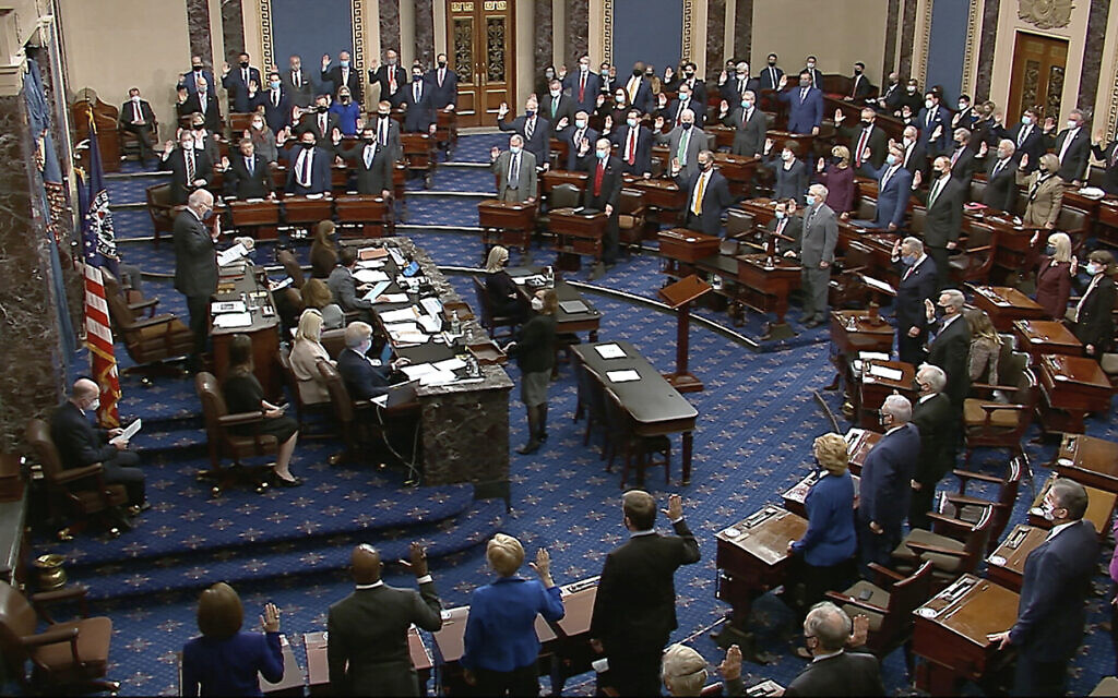In this image from video, Sen. Patrick Leahy, Democrat-Vermont, the president pro tempore of the Senate, who is presiding over the impeachment of former US President Donald Trump, swears in members of the Senate for the trial at the US Capitol in Washington, January 26, 2021. (Senate Television via AP)