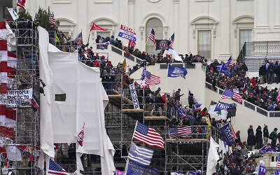 In this Jan. 6, 2021, file photo rioters loyal to US President Donald Trump storm the US Capitol in Washington. Arguments begin Tuesday, Feb. 9, in the impeachment trial of Donald Trump on allegations that he incited the violent mob that stormed the U.S. Capitol on Jan. 6. (AP Photo/John Minchillo)