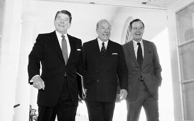 Then-secretary of state George Shultz, center, walks with then-president Ronald Reagan and vice president George Bush upon his arrival at the White House in Washington, after two days of arms talks with the Soviet Union in Geneva, on January 9, 1985. (AP Photo/Barry Thumma, File)