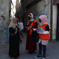 Members of Gaza's Central Elections Commission's field team register a local woman to the electoral roll, at the main road of Gaza City, February 10, 2021 (AP Photo/Adel Hana)