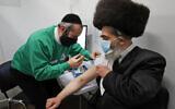 Rabbi Bieberfeld is administered a dose of the AstraZeneca coronavirus vaccine at an event to encourage vaccine uptake in Britain's Haredi Orthodox Jewish community at the John Scott Vaccination Centre in London, February 13, 2021. (AP Photo/Frank Augstein)