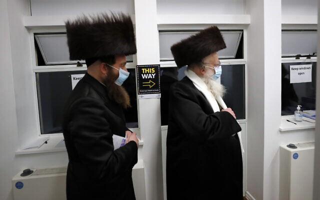 Two men from the Haredi Orthodox Jewish community arrive at an event to encourage vaccine uptake in Britain's Haredi community at the John Scott Vaccination Centre in London, Saturday, Feb. 13, 2021 (AP Photo/Frank Augstein)