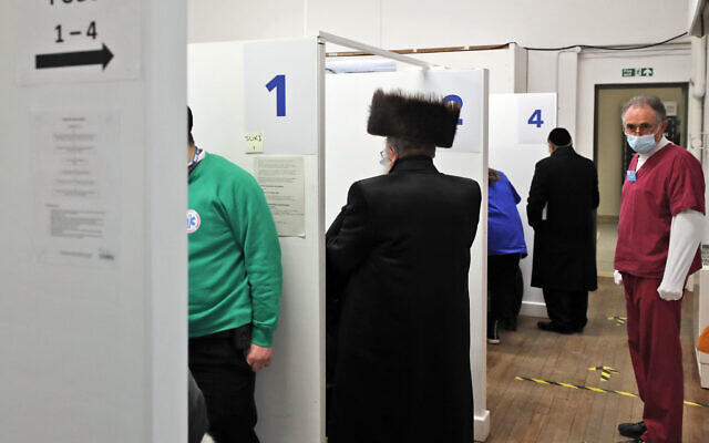 Members of the Haredi Orthodox Jewish community receive AstraZeneca vaccinations at an event to encourage vaccine uptake in Britain's Haredi community at the John Scott Vaccination Centre in London, Saturday, Feb. 13, 2021 (AP Photo/Frank Augstein)
