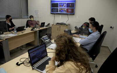 "People work at a digital task force to counter ""fake news"" on the internet, in the Health Ministry office near Tel Aviv, February 14, 2021. (AP Photo/Ariel Schalit)"
