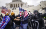 Rioters try to break through a police barrier at the Capitol in Washington, January 6, 2021. (AP Photo/John Minchillo, File)