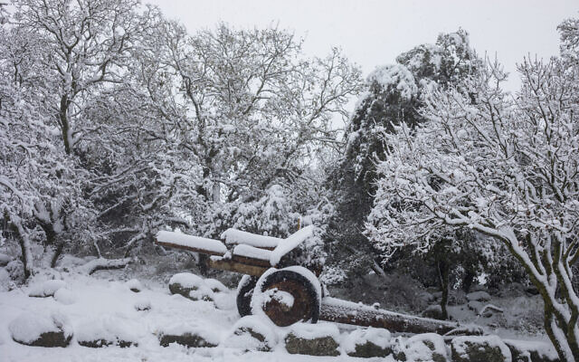 An old mobile artillery piece form Mideast wars sits covered with snow in a memorial site near the Quneitra border crossing between Syria and the Golan Heights, Wednesday, Feb. 17, 2021. (AP Photo/Ariel Schalit)