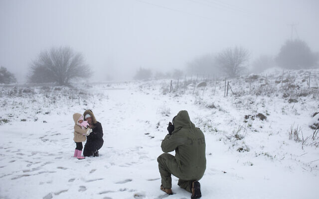 An Israeli reserve solider takes photos of his family in the snow in the Golan Heights, February 17, 2021. (AP Photo/Ariel Schalit)