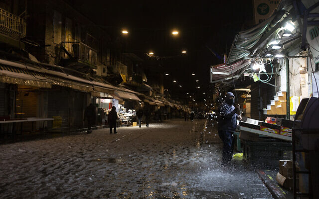 A fruit seller removes snow from his awning at the Mahane Yehuda Market, where many shops closed early due to winter weather in Jerusalem, Febrary 17, 2021. (AP Photo/Maya Alleruzzo)