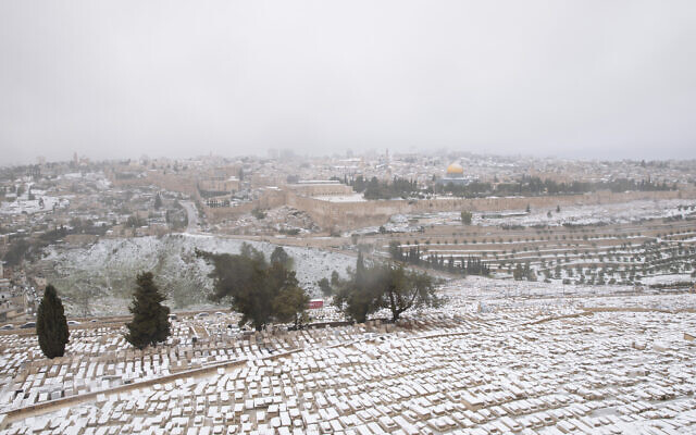 Snow covers the Mount of Olives Jewish cemetery with a view of the Dome of the Rock in the background, in Jerusalem, Thursday, Feb. 18, 2021. (AP Photo/Oded Balilty)