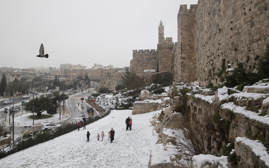 People walk in the the snow next to Jerusalem's Old City walls, Thursday, Feb. 18, 2021. (AP Photo/Oded Balilty)