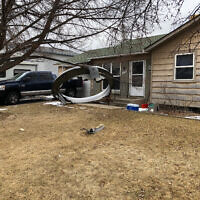 In this photo provided by the Broomfield Police Department on Twitter, debris is scattered in the front yard of a house at near 13th and Elmwood, Saturday, Feb. 20, 2021, in Broomfield, Colorado (Broomfield Police Department via AP)