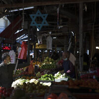 Israelis shop at a market in Tel Aviv, Israel, Sunday, Feb. 21, 2021. Israel lifted many of its coronavirus restrictions and started reopening its economy Sunday as the country's vaccination drive and third nationwide lockdown have started to bring down infections. (AP Photo/Sebastian Scheiner)